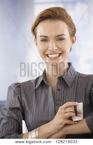 Happy young businesswoman having coffee-break, looking at camera.