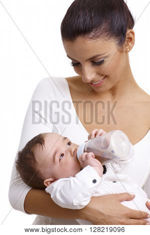 Young mother holding baby boy while baby drinking from feeding bottle, smiling.