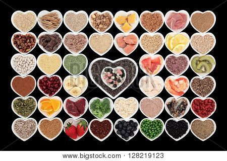 Large body building high protein health food in heart shaped bowls with meat and fish, vitamin pills, supplement powders, grains, cereals, seeds, pulses, fruit and vegetables.