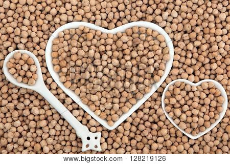 Chick pea health food in heart shaped bowls and porcelain spoon forming an abstract background.
