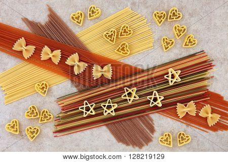 Dried pasta spaghetti food abstract background over natural hemp paper. Coloured varieties dyed with beetroot, tomato, carrot and spinach food colouring.