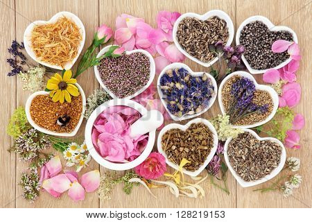 Flower and herb medicine selection used in alternative healing treatments in heart shaped porcelain bowls with mortar and pestle over oak background.