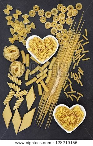 Dried pasta spaghetti food selection inn heart shaped bowls forming an abstract background over slate.