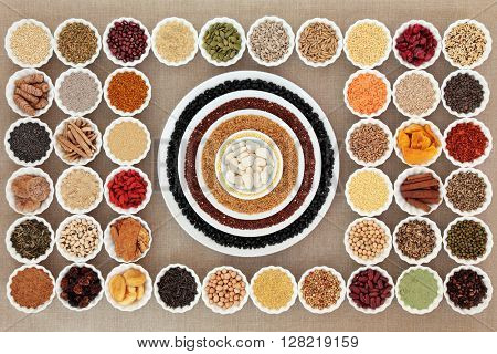 Large dried healthy superfood selection in china bowls forming an abstract background over hessian. High in antioxidants, vitamins, minerals and dietary fiber.