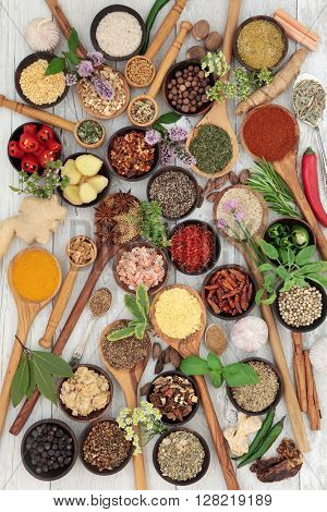 Large herb and spice fresh and dried food selection in wooden bowls and spoons over white distressed wood background.