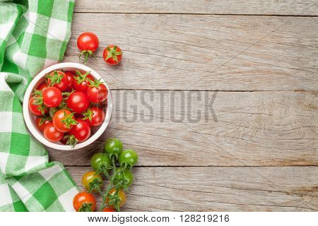 Cherry tomatoes bowl on wooden table. Top view with copy space