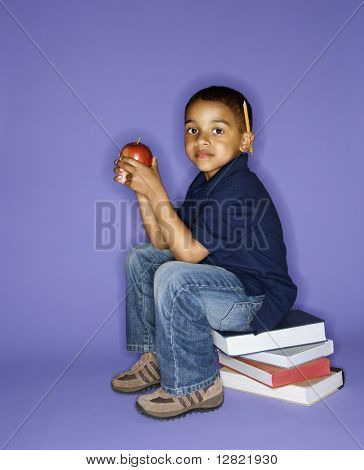 African American male child sitting on stack of books.