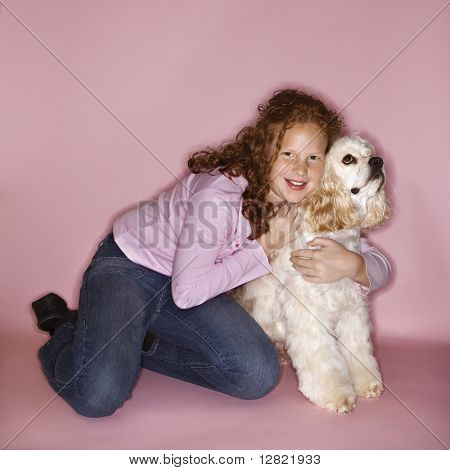 Caucasian female child hugging Cocker Spaniel dog.