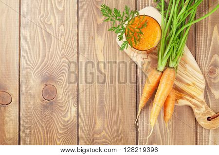 Fresh carrot juice smoothie and roots on wooden table. Top view with copy space