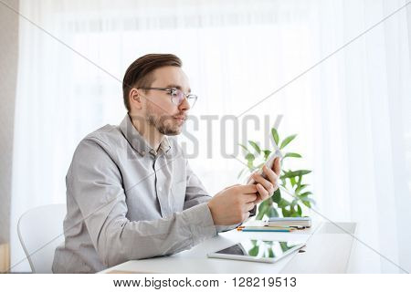 business, startup and people concept - businessman or creative male worker texting on smarphone at home office