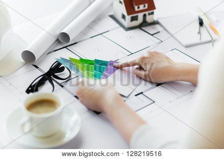 business, architecture, building, construction and people concept - close up of designer hands with color palette and blueprint