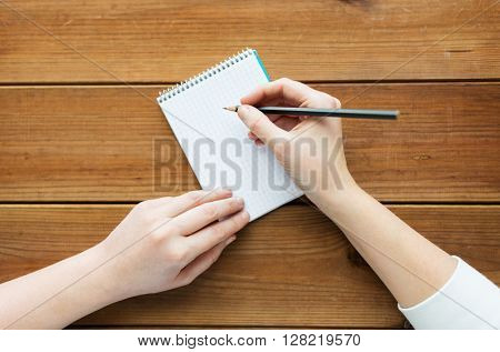education, business and people concept - close up of woman or student with pencil writing to notepad on wooden table