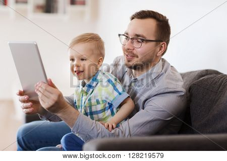 family, childhood, fatherhood, technology and people concept - happy father and son with tablet pc computer playing or having video chat at home