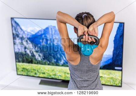 Home active lifestyle girl lifting kettlebell weights watching smart tv program following fitness routine. Young woman training triceps in living room working out arms with video workout exercises.