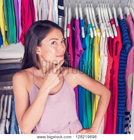 Home closet or store clothing rack changing room. Woman choosing her fashion outfit. Shopping girl thinking what dress to wear to go on a date. New trendy colorful clothes in organized clean walk-in.
