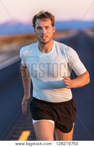 Athlete endurance runner man long distance running with focus and determination on desert road at sunset. Sportsman training in compression sports t-shirt and shorts activewear in summer landscape.