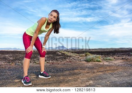 Trail runner taking a running break breathing tired exhausted on difficult run race. Female athlete resting in dramatic volcano landscape on path in summer nature mountains. Woman training hard.