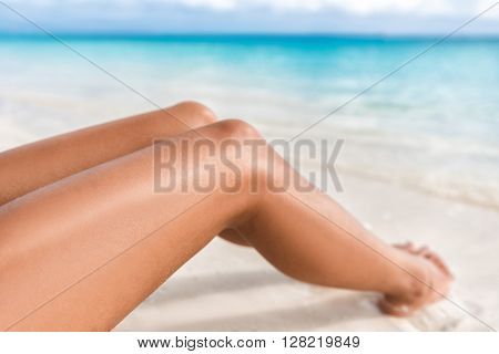 Sexy suntan bikini woman legs relaxing lying down on white sand beach summer vacation. Beauty skincare sun aging protection body care of tanned skin. Epilation laser or shaving concept.