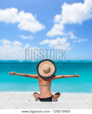 Happy freedom carefree bikini woman enjoying summer beach vacation with arms up cheering in success. Girl feeling free with sun hat relaxing sunbathing on holidays. Caribbean south tropical travel.
