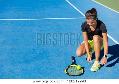 Sports woman Asian happy athlete getting ready for playing tennis tying laces of her running shoes on outdoor blue hard court. Professional player preparing for summer tournament game.