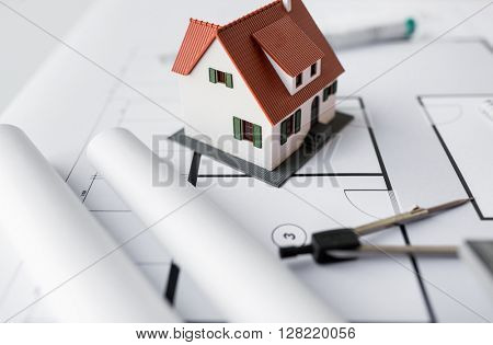 architecture, building, construction, real estate and home concept - close up of living house model and compass on blueprint