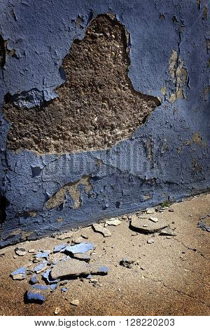 Old blue plaster wall crumbled broken pieces