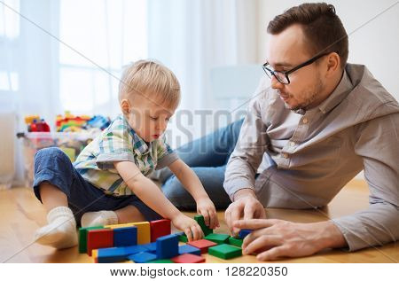 family, childhood, creativity, activity and people concept - happy father and little son playing with toy blocks at home