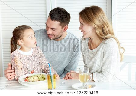 family, parenthood, communication and people concept - happy mother, father and little girl eating pasta for dinner and talking at restaurant or cafe