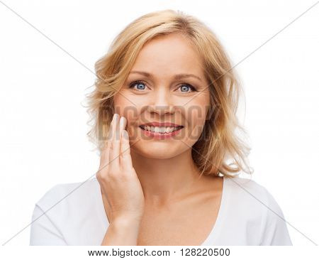 beauty, people and skincare concept - smiling woman in white shirt touching face
