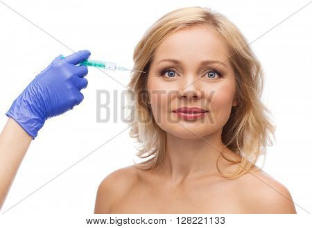 beauty, anti-aging cosmetic surgery concept - smiling woman face and beautician hand in glove with syringe making injection to eye contour area
