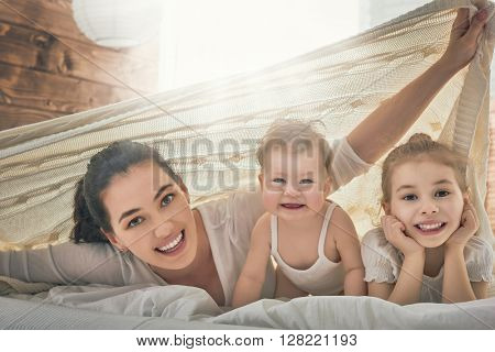 Happy loving family. Mother and her daughters children girls playing in bed.