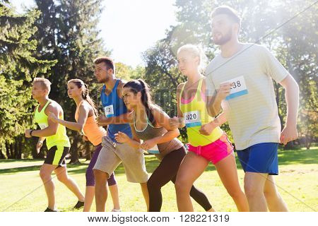fitness, sport, race and healthy lifestyle concept - group of teenage friends or sportsmen with badge numbers on start of running marathon outdoors