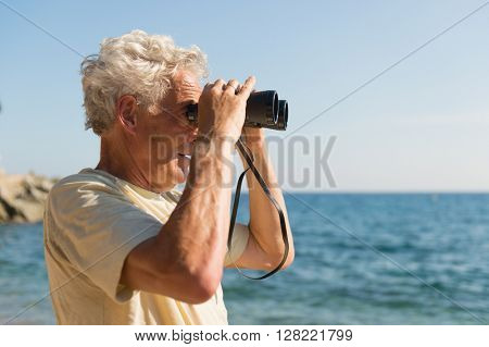 Senior man with spy glasses at the beach