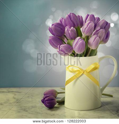Purple tulip bouquet on blue background