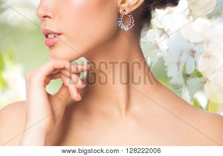 glamour, beauty, jewelry and luxury concept - close up of beautiful woman face with earring over natural spring cherry blossom