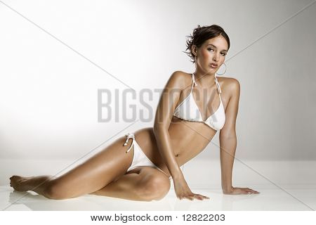 Caucasian young adult woman in bikini sitting on floor and looking at viewer.