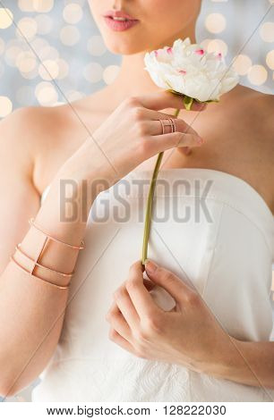 glamour, beauty, jewelry and luxury concept - close up of beautiful woman with golden ring and bracelet holding flower over holidays lights background