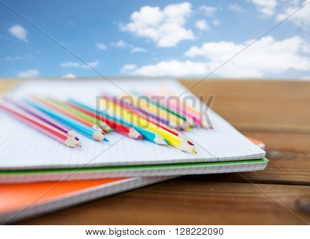 school, education, drawing and object concept - close up of crayons or color pencils on notebook paper over blue sky and clouds background
