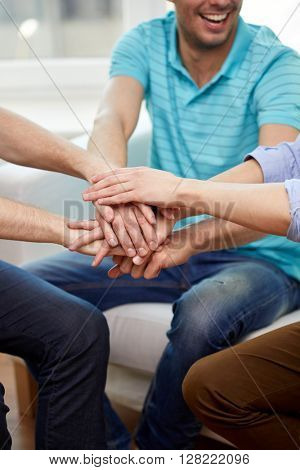 teamwork, friendship, unity, cooperation and gesture concept - close up of happy friends holding hands on top of each other