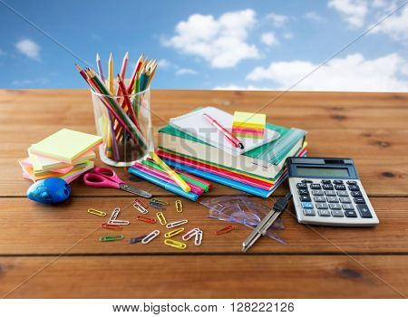 education, school supplies, art, creativity and object concept - close up of stationery on wooden table over blue sky and clouds background