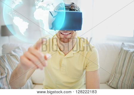 technology, global, international, gaming and people concept - happy young man in virtual reality headset or 3d glasses playing video game with earth or planet hologram at home