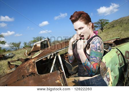 Angry tattooed Caucasian woman with fists clenched ready to fight in junkyard.