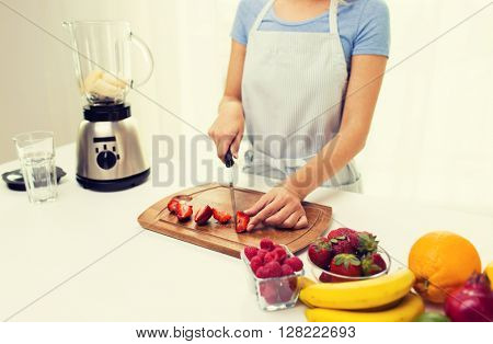 healthy eating, cooking, vegetarian food, dieting and people concept - close up of woman chopping strawberry at home