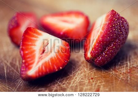 fruits, berries, diet, eco food and objects concept - close up of fresh ripe red strawberries on cutting board