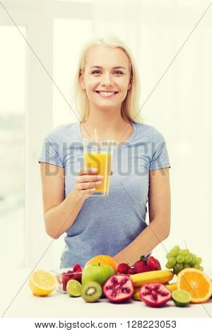 healthy eating, vegetarian food, dieting and people concept - smiling woman drinking fruit juice from glass at home