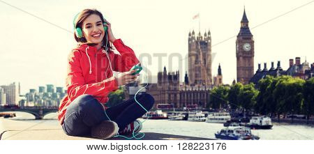 technology, travel, tourism, vacation and people concept - smiling young woman or teenage girl with smartphone and headphones listening to music over london city and thames river background