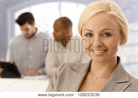 Closeup portrait of beautiful young blonde businesswoman smiling, looking at camera.