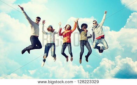 people, freedom, happiness and teenage concept - group of happy friends in sunglasses jumping high over blue sky and clouds background