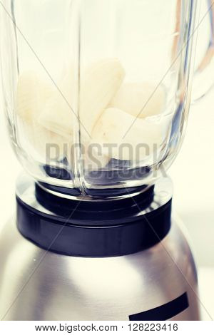 healthy eating, cooking, kitchen appliances and technology concept - close up of blender shaker with bananas