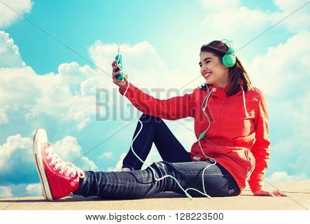 technology, lifestyle and people concept - smiling young woman or teenage girl with smartphone and headphones listening to music outdoors over blue sky and clouds background
